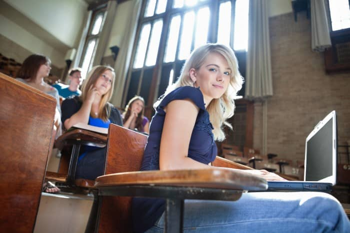 Portrait of college girl using laptop while students sitting in background